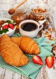 新月形面包、咖啡、格兰诺拉麦片和草莓 库存图片