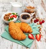 新月形面包、咖啡、格兰诺拉麦片和草莓 图库摄影