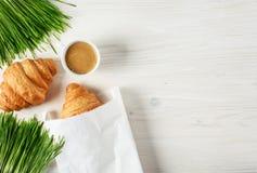 新月形面包、咖啡和发芽的麦子在木背景 免版税库存图片
