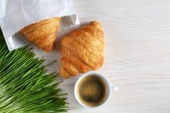 新月形面包、咖啡和发芽的麦子在木背景 免版税库存照片