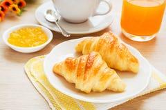新月形面包、咖啡杯和汁液在木桌上 免版税图库摄影