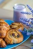 新月形面包、小圆面包用葡萄干在一块蓝色板材和蓝莓酸奶在玻璃瓶子 免版税库存照片