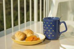新月形面包、杏子和咖啡一顿早餐在大阳台 库存图片