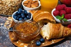 新月形面包、橙色果酱和新鲜的莓果早餐,特写镜头 库存图片