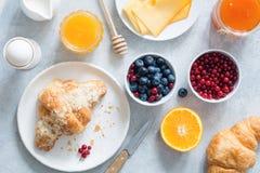 新月形面包、蜂蜜、乳酪、果酱、新鲜的莓果和果子 大陆的早餐 库存图片