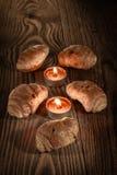 新月形面包、酥皮点心、松饼、蛋糕和酥皮点心在美好的木背景与蜡烛4 免版税库存图片