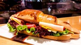 新月形面包三明治用火腿、切达干酪、西红柿和绿色 免版税库存图片