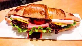 新月形面包三明治用火腿、切达干酪、西红柿和绿色 免版税库存照片