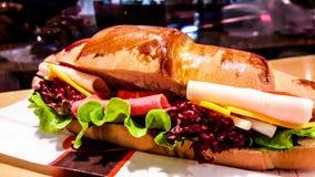 新月形面包三明治用火腿、切达干酪、西红柿和g 免版税库存照片