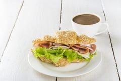 新月形面包三明治用莴苣、烟肉、乳酪在白色板材和咖啡在木背景 免版税图库摄影