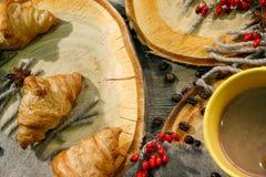 新月形面包和一杯咖啡木表面上的在一个羊毛一揽子和红色莓果中 秋天动机 库存照片
