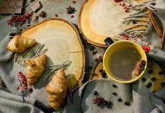 新月形面包和一杯咖啡木表面上的在一个羊毛一揽子和红色莓果中 秋天动机 免版税库存图片