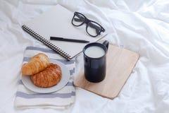 新月形面包和书在工作表上早晨 免版税库存图片