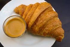 新月形面包和咖啡在一块白色板材用早餐 免版税库存照片