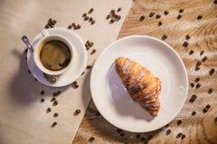 新月形面包和咖啡在一张木桌上,咖啡粒在桌上驱散了 库存照片