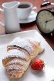 新月形面包和咖啡在木背景 库存图片