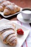 新月形面包和咖啡在木背景 免版税库存图片
