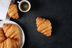新月形面包和咖啡在黑暗的背景 免版税库存图片