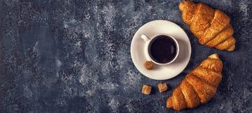 新月形面包和咖啡在黑暗的背景 免版税图库摄影
