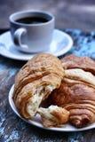新月形面包和杯子咖啡 库存照片