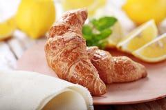 新月形面包和柠檬早餐 库存照片