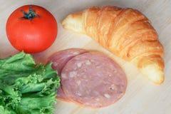 新月形面包和火腿为烹调三明治做准备 免版税库存照片