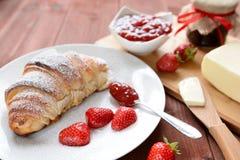 新月形面包和草莓酱在木背景 库存照片