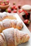 新月形面包和草莓酱在木背景 图库摄影