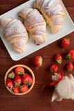 新月形面包和草莓酱在木背景 免版税库存图片