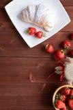 新月形面包和草莓酱在木背景 免版税图库摄影