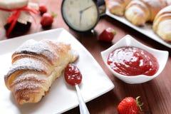 新月形面包和草莓酱在木背景 库存图片