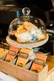 新月形面包和Brrowine在玻璃展示在咖啡店 库存照片