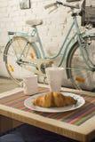 新月形面包杯子和葡萄酒在咖啡店内部骑自行车 免版税库存图片
