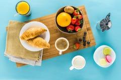 新月形面包用在厨房书桌上的莓果用咖啡和橙汁 免版税图库摄影