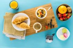 新月形面包用在厨房书桌上的莓果用咖啡和橙汁 库存照片