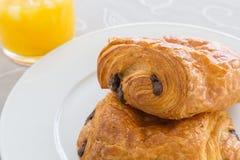 新月形面包用巧克力填装在一块白色板材的,在一个白色盘子的橙汁 库存图片