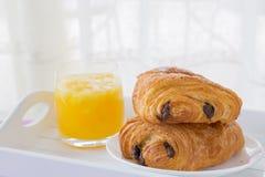 新月形面包用巧克力填装在一块白色板材的,在一个白色盘子的橙汁 免版税库存图片
