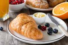 新月形面包用橙汁、黄油、果酱和新鲜水果 免版税库存图片