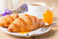 新月形面包用橙色果酱和咖啡。 免版税库存照片