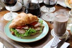 新月形面包用火腿,绿色莴苣,在板材的蕃茄切片 免版税图库摄影