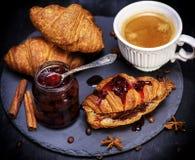 新月形面包用草莓酱和白色杯子用咖啡 免版税库存照片