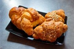新月形面包用黄油和谷物 库存照片