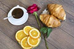 新月形面包用黄油、咖啡和桔子早餐 库存照片