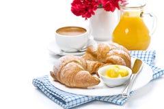 新月形面包用黄油、咖啡和汁液早餐 免版税图库摄影