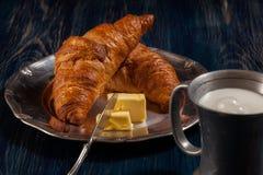 新月形面包用黄油和一杯牛奶 库存照片