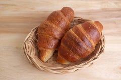 新月形面包篮子在木桌上的 免版税库存照片