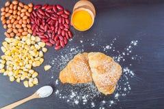 新月形面包面包、新鲜的鸡蛋在面粉和花生和红色小扁豆和玉米在黑木黑板 库存照片