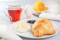 新月形面包,煮沸的鸡蛋,茶,黄油,果酱 利器,餐巾 早餐大陆法语 免版税库存照片