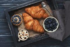 新月形面包,蛋糕用蓝莓,咖啡用在一个木盘子的蛋白软糖有餐巾的 木黑暗的背景,顶视图 库存图片