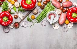新有机菜和调味料品种烹调与灰浆、杵和木匙子的鲜美素食主义者的在灰色concre 库存照片